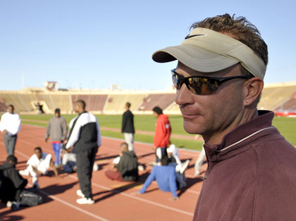 City College men's track and field coach Rob Dewar observes the team doing warm-ups in January before practice at Hughes Stadium. Photo by Robert Paul.
