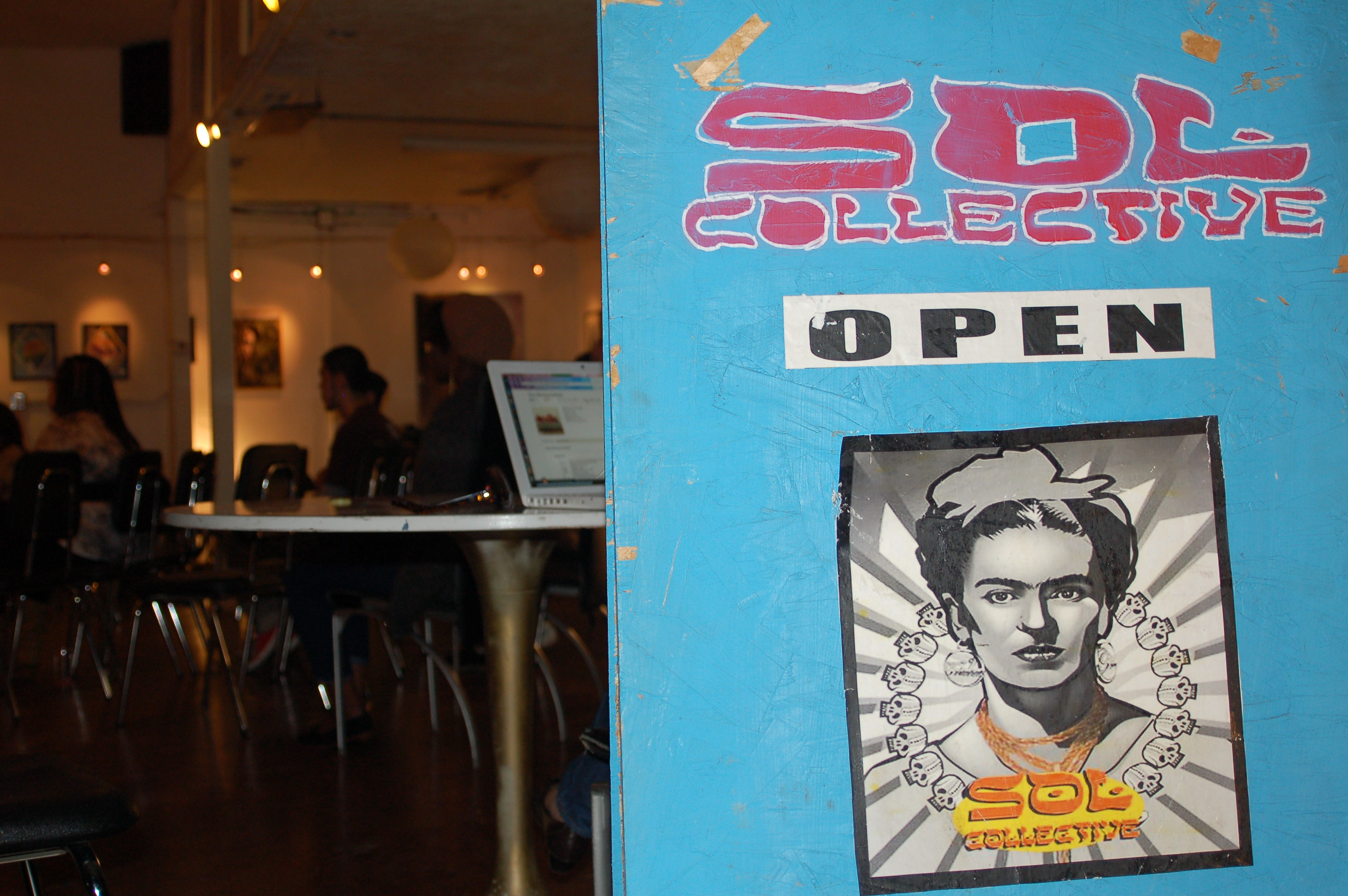 Photo of Sol Collectivce sign displayed inside the door of the building.