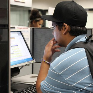 A male student is reading a computer screen.