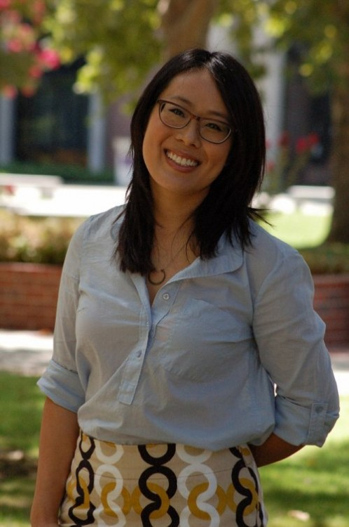A woman in glasses and dark hair wearing a light blue blouse stands outside in the City College quad.