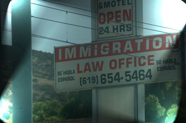 An immigration office sign with a phone number.