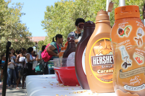 Bottles of chocolate syrup sit on a table in front of a line of students.