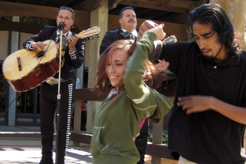 A male and female student smile as they dance to a Mariachi band.