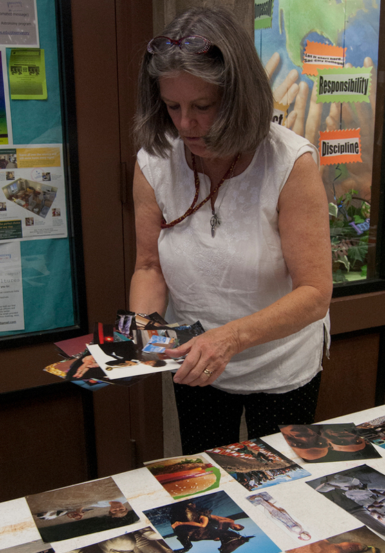 A woman arranging photographs near a table inside a hallway.