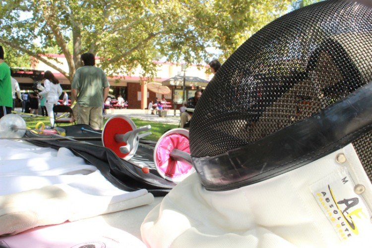 A fencing mask and swords rest on a table outside in the Quad.