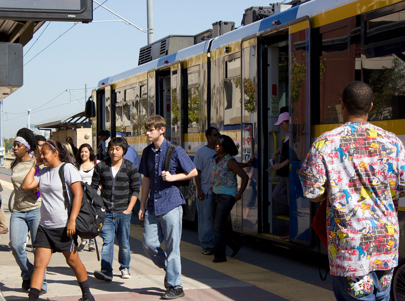 Students are getting on and off of a light rail train at the light rail station.