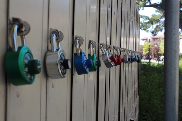 A row of lockers with multi colored locks attached.