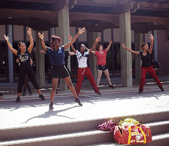 Female dance students have their arms in the air.