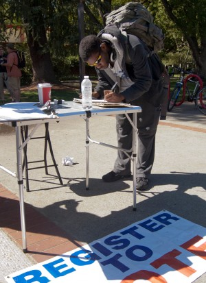 A male student signing paperwork on a table outside in the quad.