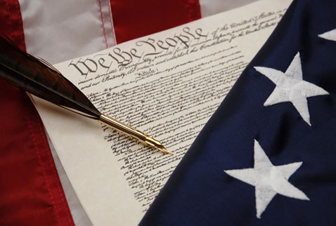 A pen and a flag lie across a printed copy of the U.S. Constitution.