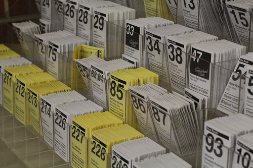 Printed white and yellow Sacramento lightrail schedules placed in rows.