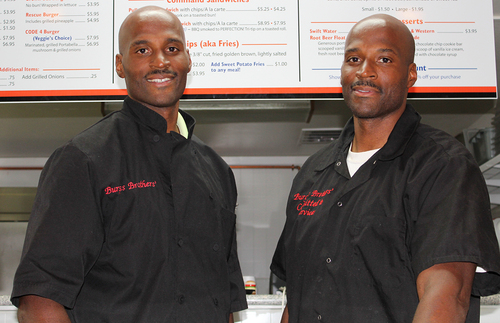 Two men stand in front of a menu.