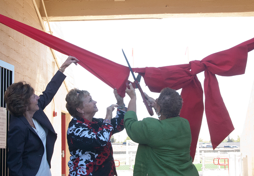 Two women cut a big red ribbon.,