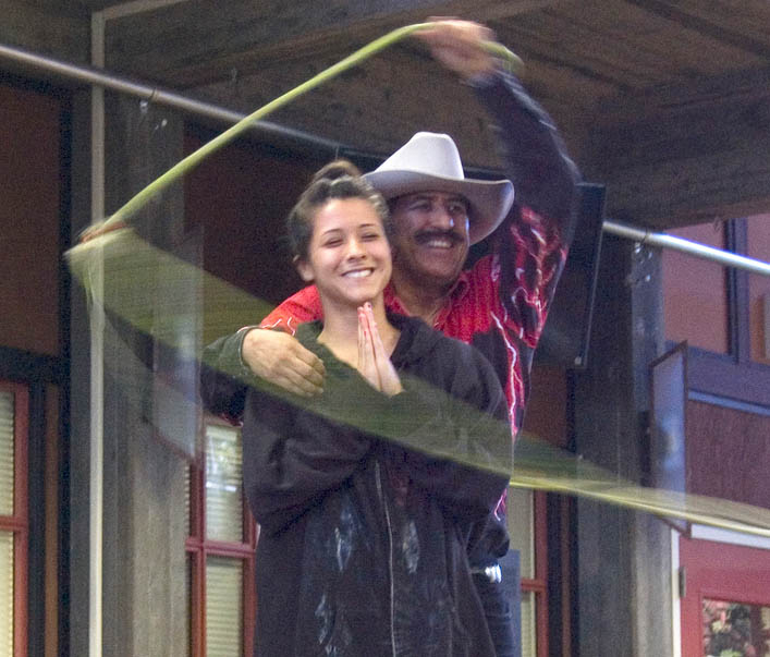 A man in a cowboy hat swirls his lasso around a female student.