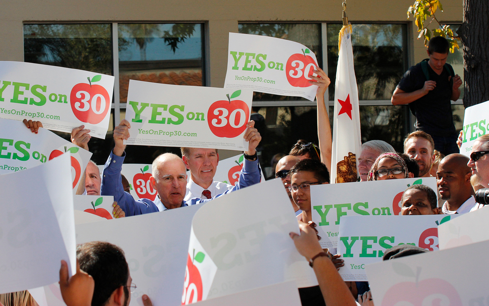 "Gov. Jerry Brown held up his ""Yes on 30"" banner and excited City College students and supporters followed.  Kate Paloy 