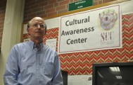 A man standing in front of the Cultural Awareness Center sign.