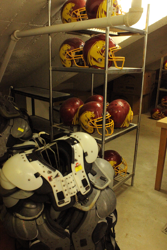 Football helmets and shoulder pads located in a storeroom.