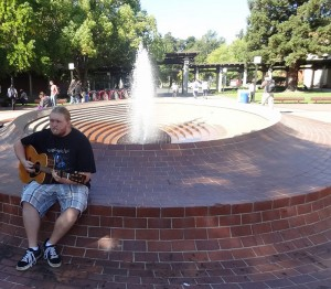 A man sitting on a fountain playing his guitar.