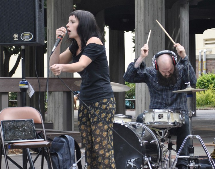 A woman sings while a a man plays drums during a performance in the quad.