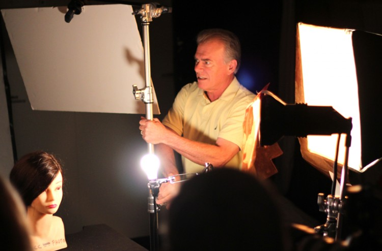 A man is adjusting lights in a photography studio.