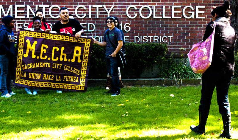 A group of students posing for a group photo in front of City College.