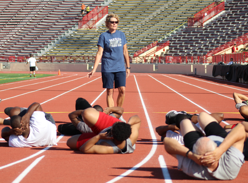 A woman instructs a group of students stretching on the track at Hughes Stadium.
