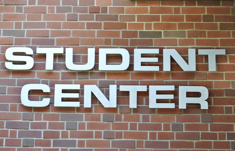 A sign of the Student Center on a brick wall.