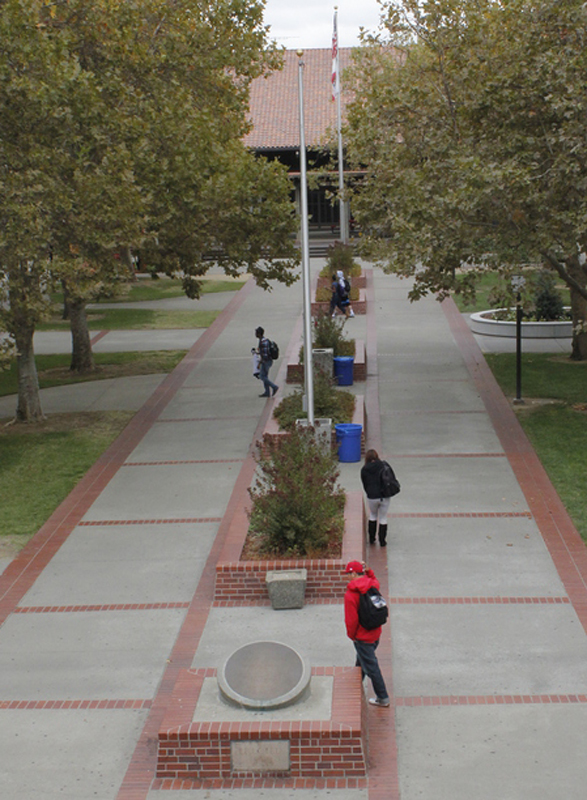 A handfull of students walk through an almost empty quad.