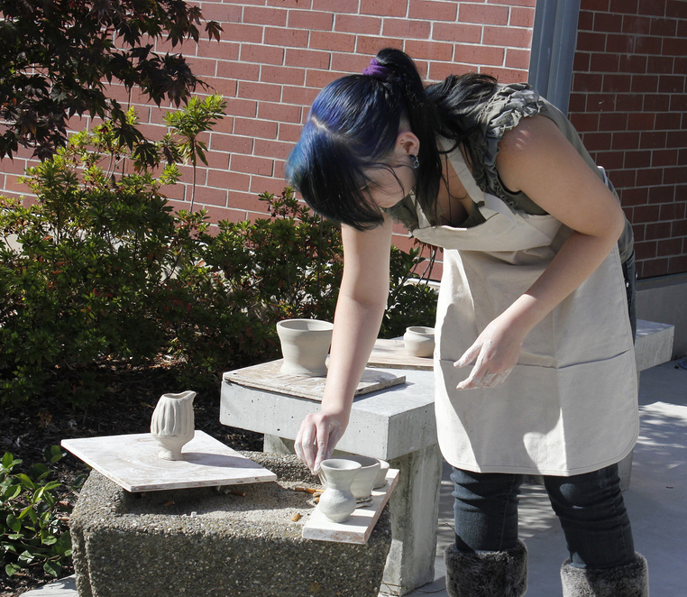 A woman places ceramic pieces outside on a bench