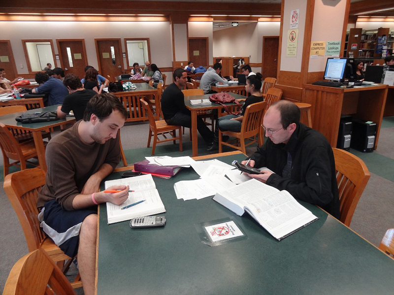 Two men are studying at a table inside the library.