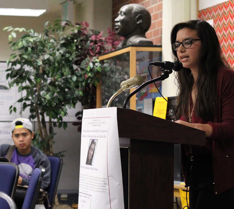 A woman gives a speech to a group of students.
