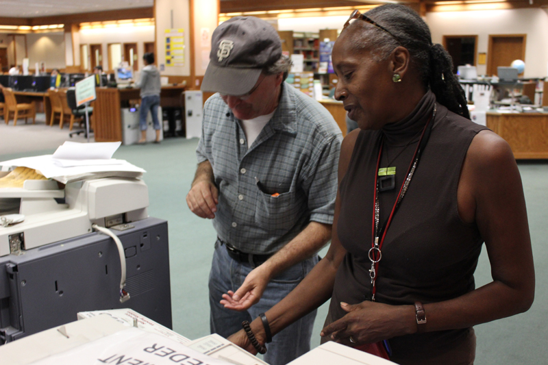 Johni Quinn-Berry, a student librarian, helps a student with the copying machine, one of the many jobs she performes daily. Tony Wallin | dylanwaittswallin.express@gmail.com