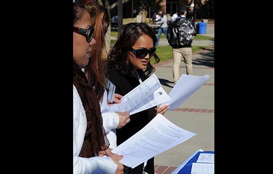 Cosmetology student Phiv Tan, far right, looks over job announcements on February 11 at the City College quad, regarding job openings at the Sacramento Children's Home. | Rafael Baez | rebaez@sbcglobal.net