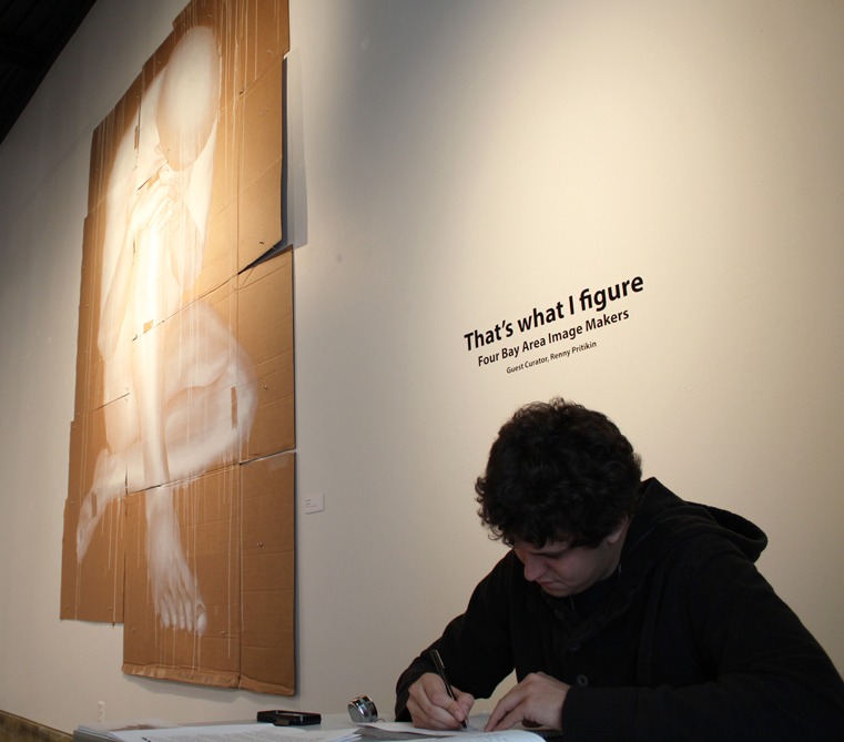 """Vasiliy Savchenko, front desk attendant for the Kondos Gallery, works on a drawing while waiting for art appreciators to come to see the gallery's latest exhibit """"That's what I figure."""" 