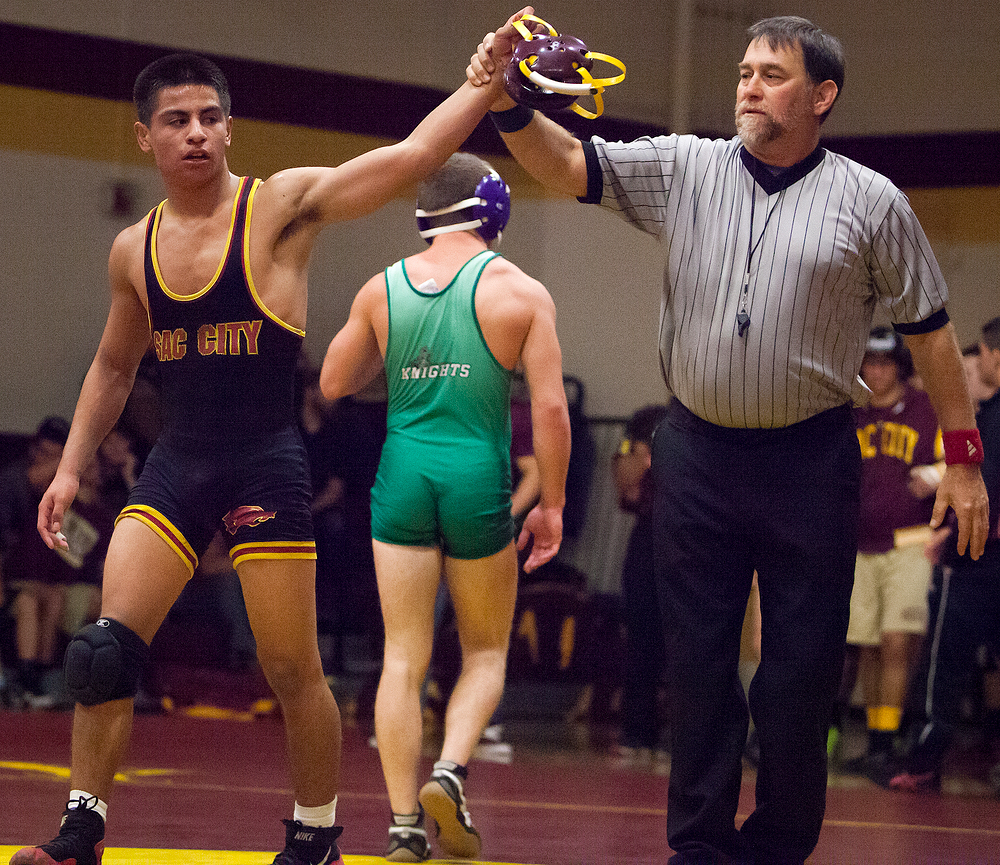 Official Tony Trabucco holds arm up of City College freshman Albert Landeros after his 14-2 win Oct. 16 over opponent Joseph Holcomb, Shasta College sophomore Oct. 17.  (Multimedia Editor   Dianne Rose   dianne.rose.express@gmail.com)