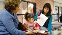City College student Yeny Lopez looks on while Ana Rodriguez, a Head Start teacher for the Sacramento region, reads with Lopez's 2-year-old daughter Analy Estevez outside the City College's counseling office March 3. Photo by Elizabeth Ramirez | Staff Photographer | elizabethramirezexpress@gmail.com