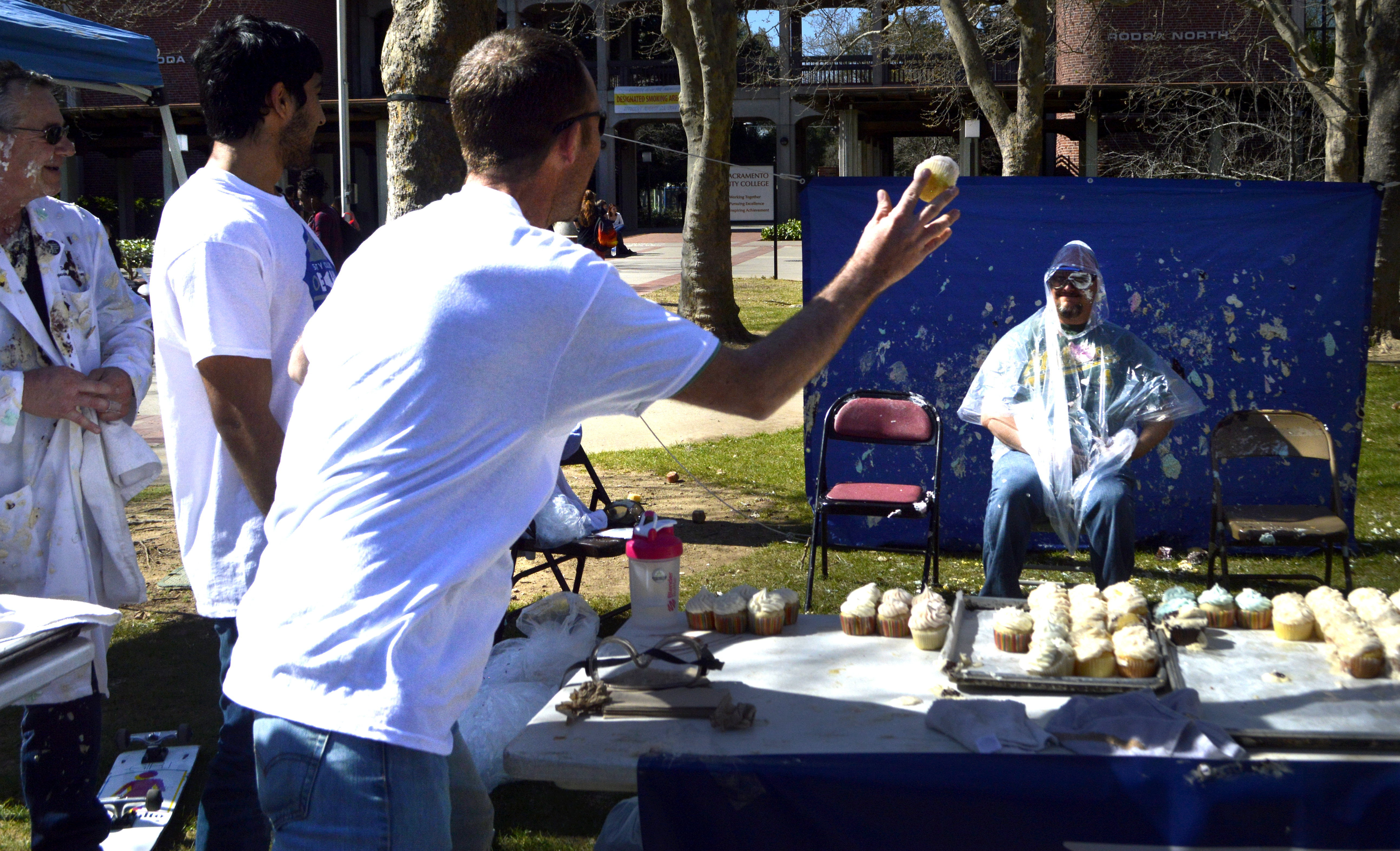 City College club,  Omechs booth, charges $1 to throw a cupcake at professors for club day. Mechanical engineering student, Levi Hopson throws a cupcake at math professor Joseph Stever March 5,2015. Emily Foley | Photo Editor |