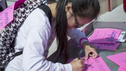 City College psychology student Maria Nguyen, creates a flyer before joining the annual cancer awareness walk around Hughs Stadium with other students and faculty March 19. Nguyen is one of 180 college students around the US participating in a national fundraiser. 4K for Cancer helps raise awareness to the Ulman Cancer Fund for young adults programs. Luisa Morco | Staff Photographer