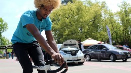 City College mechanical engineering student Isaias Iglesias, riding his bike through campus. Electrical cars are displayed for Earth week in front of the Performing Arts Center April 21, 2015. Vhonn Ryan Encarnacion | Staff Photographer | ryanvhonn@gmail.com