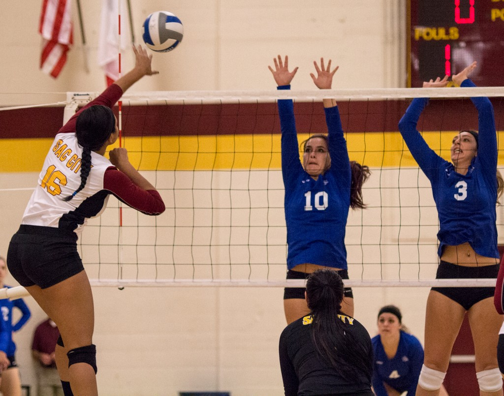 City College outside hitter Regan Bradley hits the ball between two defenders for a point during the second set of the match against Modesto Junior College in the North Gym Nov. 3, 2015. (Photo: Kristopher Hooks   Editor in Chief   khooksexpress@gmail.com)