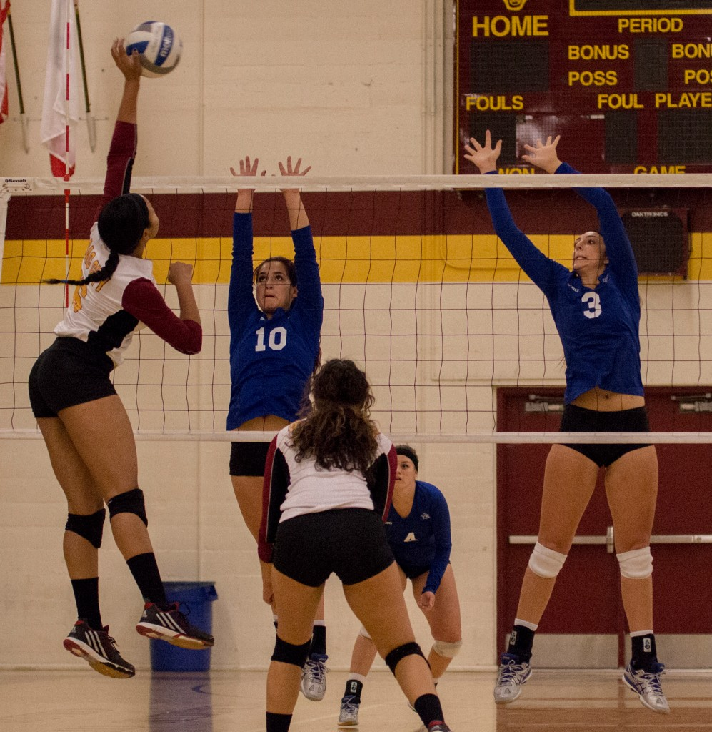 City College outside hitter Regan Bradley hits the ball between two defenders during the second set of the match against Modesto Junior College in the North Gym Nov. 3, 2015. (Photo: Kristopher Hooks   Editor in Chief   khooksexpress@gmail.com)