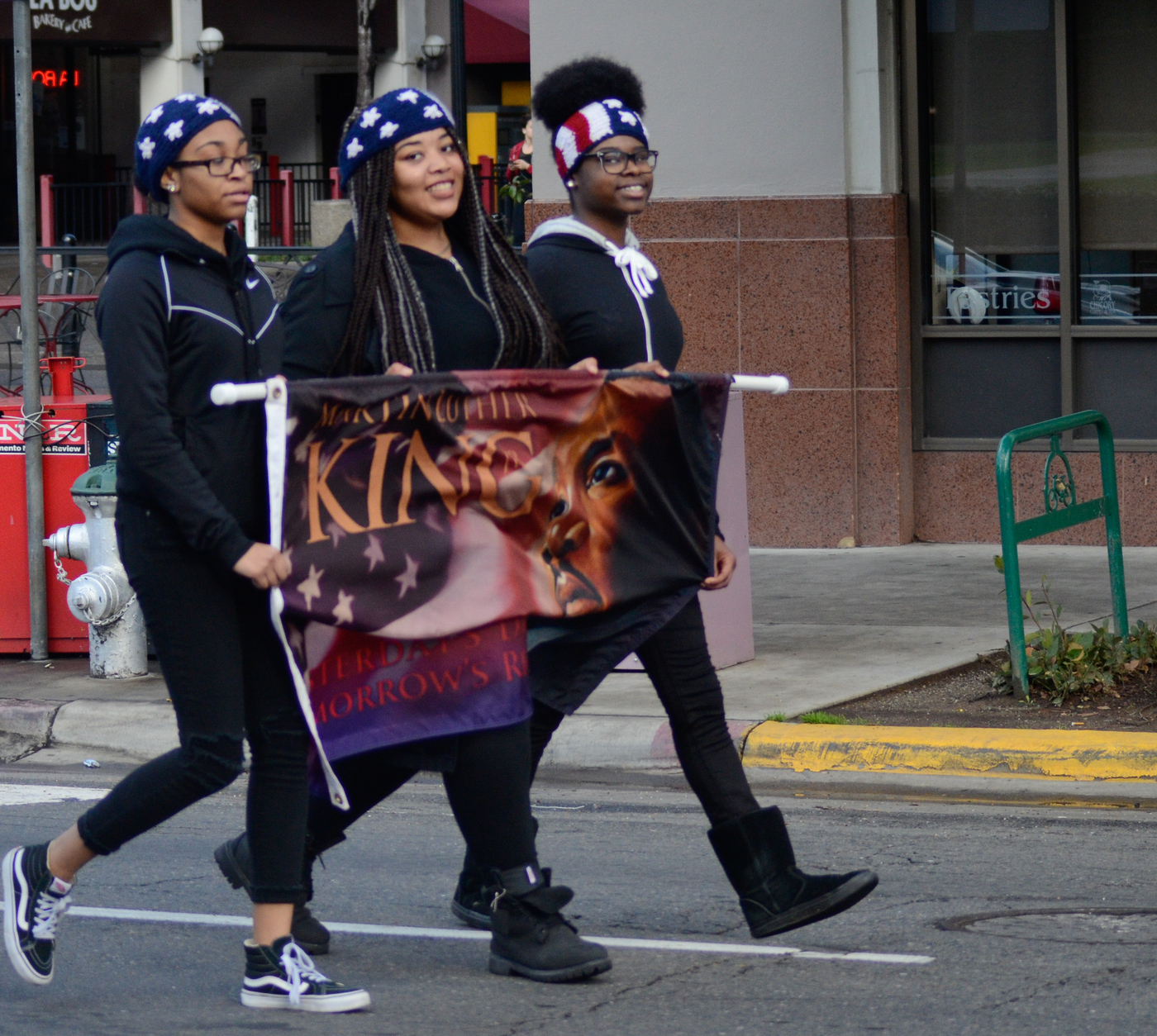 MLK March 1-18-16 Downtown  Sacramento, CA. A group of young women participants walks in the MLK  March holding a banner with an image of Dr. Martin Luther King, Jr. They are heading towards the Sacramento Convention Center   Chris Williams, Staff Photographer. | Chriswexpress@gmail.com
