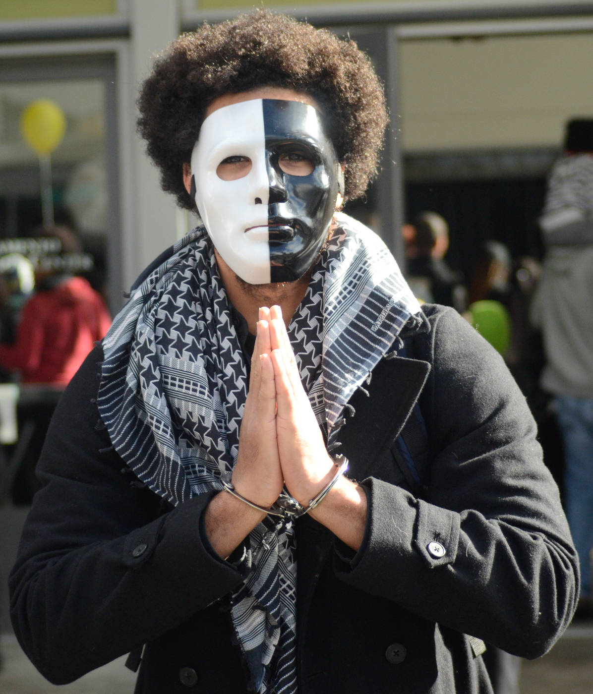MLK March 1-18-16 Downtown Sacramento, CA. In front of Sacramento Convention Center. Jonathan Shaw wearing a white and black mask and handcuffs, posing for a photo. Chris Williams Staff Photographer. | Chriswexpress@gmail.com