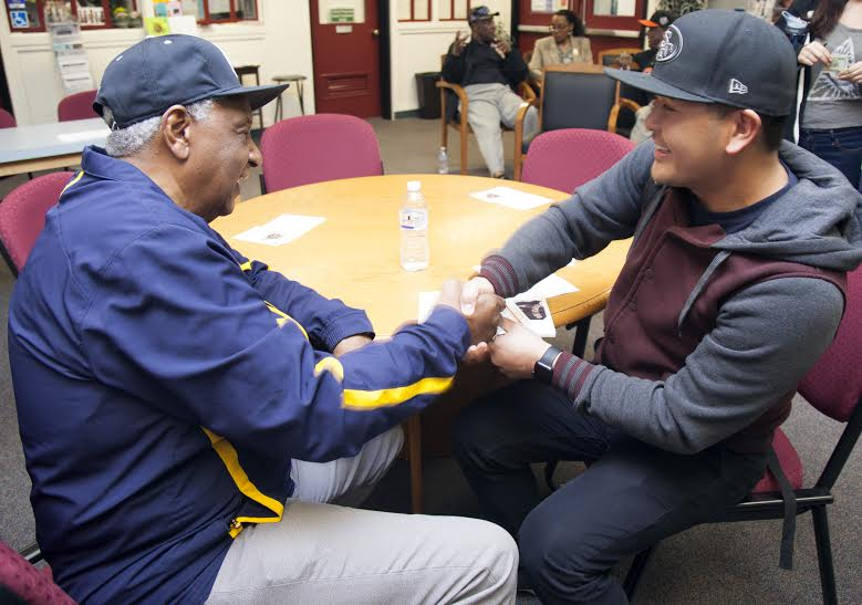 Former National Negro Baseball League player Dennis Biddle signs his baseball card for City College student Eric Dipad, occupational therapy major. Biddle was the youngest person to play in the National Negro Baseball League. Feb. 11, 2016. Diane Mitchell, Guest Photographer.| 4jedimi@gmail.com