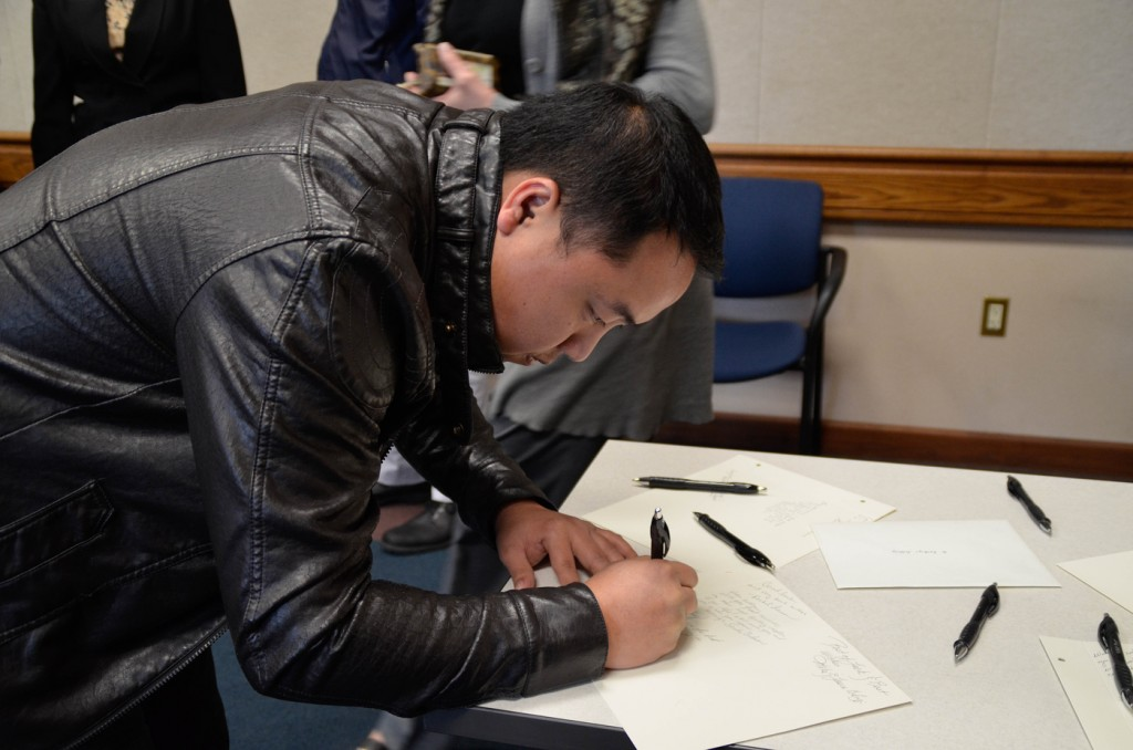City College employee Micheal Thao signing a good luck note for Jeffery. Jan. 28, 2016. Barbara Williams, staff photgrapher. | BarbarajExpress@gmail.com