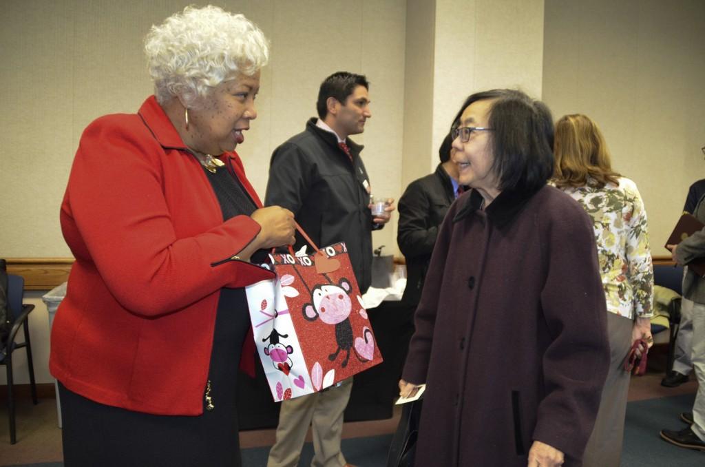 City College retired international counselor Susan Fong giving Jeffery a gift at Jeffery's reception on Jan. 28, 2016. Barbara Williams, staff photgrapher. | BarbarajExpress@gmail.com
