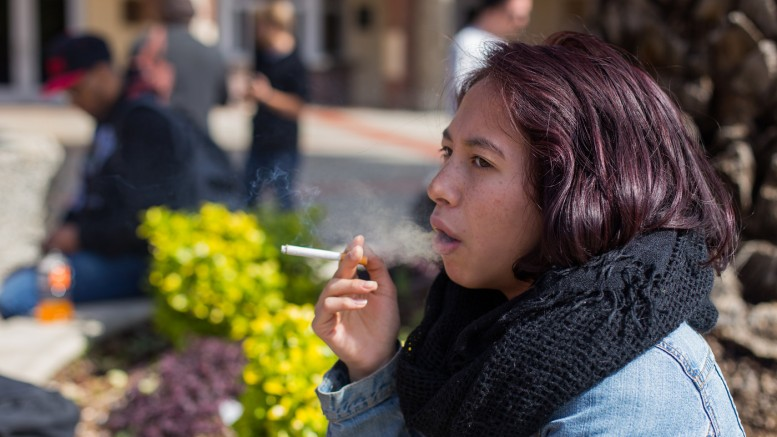 City College student Naomi Jones, pychology major, smokes a cigarette in front of the Performing Arts Center on March 14, 2016. Hector Flores, Staff Photographer. | hectorfloresexpress@gmail.com