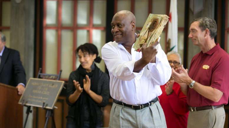 City College Vice President Michael Pointdexter holds up a book from the time capsule during its enveiling at the Sacramento City College 100th Anniversary on Oct. 15, 2016. Hector Flores, Staff Photographer. | hectorfloresexpress@gmail.com