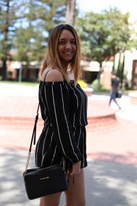 """Emily Hevans, 18, majors in criminology and minors in psychology. She sports a cute, black off the shoulder single piece romper paired with a matching black Michael Kors purse. Despite her put-together look, Hevans says that she """"saw it was warm out and just threw it on."""" Ulysses Ruiz 