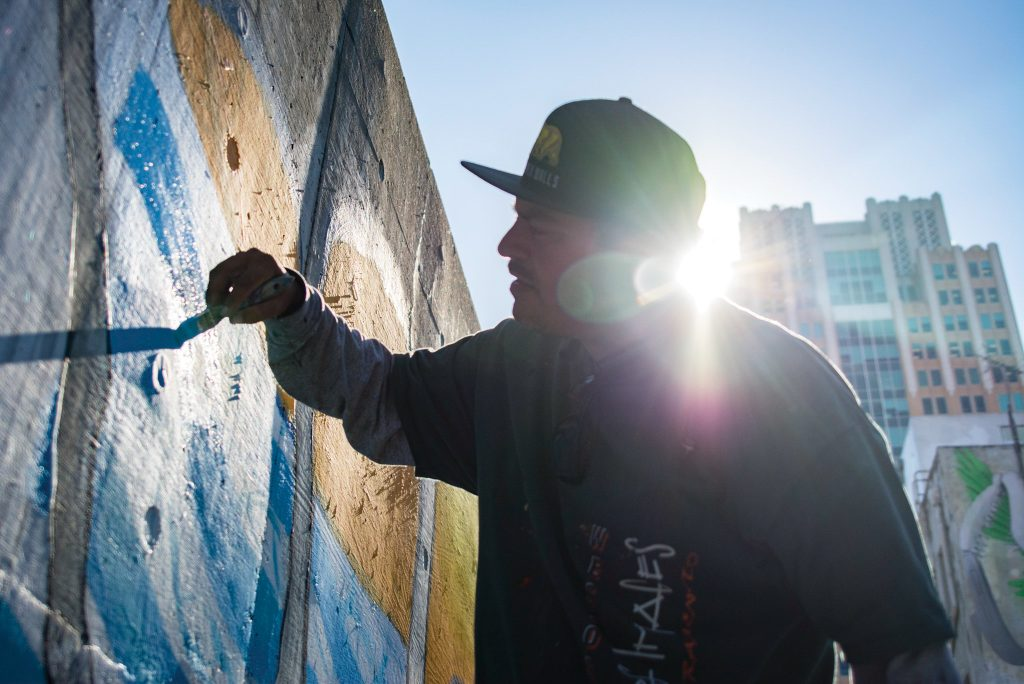 """Markos Egure works on the """"Humanity"""" mural Aug. 28, a work made by the ARTners Collaborative. The mural is located on Improv Alley between 7th and 8th streets. Jason Pierce   Photo Editor   jpierce.express@gmail.com"""